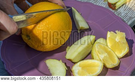 Close-up View Of Cutting Orange Juice, Apple And Lemon. Healthy Food On The Table. Fruit Chopping. H