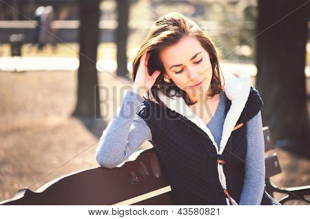 Portrait Of Young Girl Sitting On A Bench