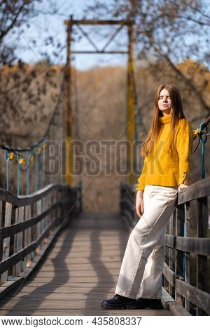 A Red-haired Girl Stands On A Wooden Bridge In An Orange Sweater And Looks At The Autumn Sun. Relaxe