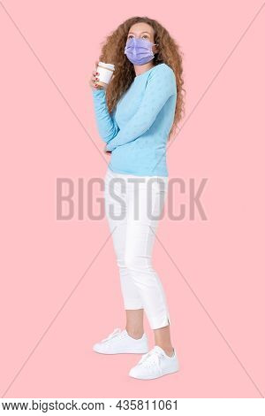 Woman holding coffee cup during the new normal