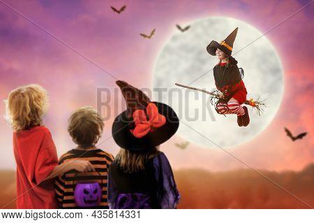 Little Witch Flying Broom On Halloween Night. Kids Watch Huge Full Moon And Bats In Dark Window. Chi