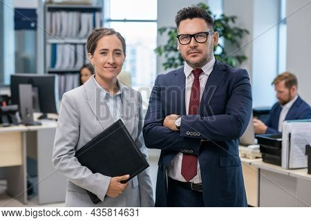 Two well-dressed employees standing in front of camera in office environment