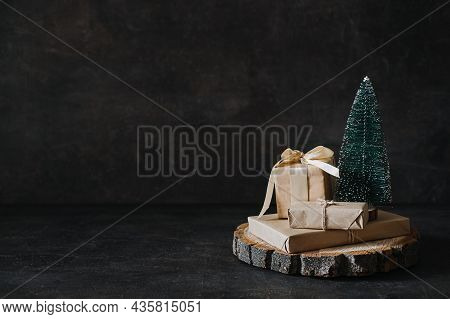 Christmas Banner, Xmas Minimal Dark Background With Craft Gift Boxes And Cone Toy Christmas Tree On
