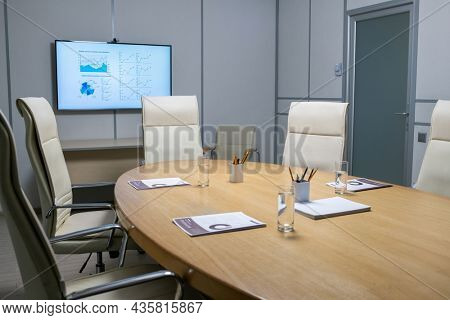 Interior of boardroom with documents and glasses of water on large table surrounded by armchairs