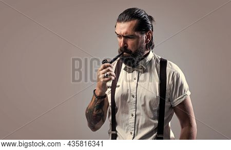 Formal Male Smokier. Old Fashioned Bearded Hipster Smoking Pipe Trendy Man In Suspenders And Bow Tie
