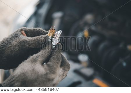 Spark Plug Replacement Work, Hand Of The Auto Mechanic Holding The Old Spark Plug On Blurred Engine
