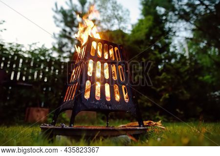 A Burning A Bonfire In A Fire Bowl On A Summer Evening In The Backyard. Burning Firewood In A Fire B
