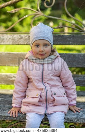 Little Girl In The Park. Girl Wearing A Hat And Jacket In The Open Air.