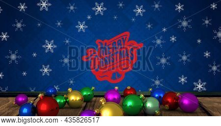 Image of baubles and snowflakes over merry christmas text on blue background. christmas, tradition and celebration concept digitally generated image.