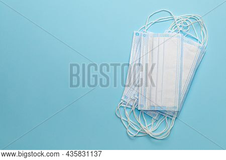 Stack Of Clean New Medical Masks On A Blue Background. Copy Space For Text
