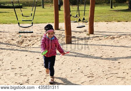 The Girl Plays On The Playground In The Fall. Girl In A Red Jacket In A Beautiful Autumn On The Play