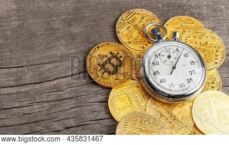 Stopwatch And Bitcoin. Cryptocurrency Gold Coins And Time On A Wooden Table. Fast Money On Bitcoin.