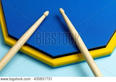 Drum Sticks And Training Mat On A Blue Background