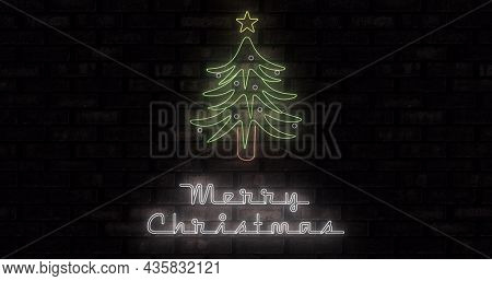 Image of neon merry christmas text and christmas tree on black background. christmas, winter, tradition and celebration concept digitally generated image.