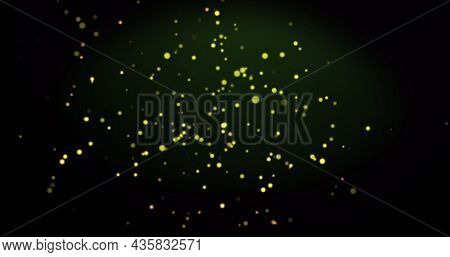 Image of warm glowing yellow spots on green background. light, colour and movement concept digitally generated image.