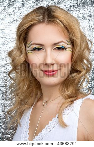 Pretty young woman portrait with bright yellow and blue make-up and long eyelashes