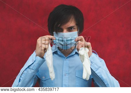 Young Man In A Medical Mask With Gloves And Glasses On A Red Background. Male Portrait. Virus Protec