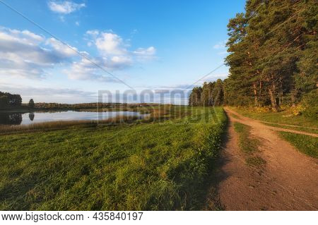 Dirt Village Road Between Forest And Lake On A Beautiful Evening In Early Autumn. Pushkin Mountains,