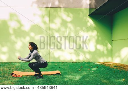 Sporty Young Woman Doing Squat Exercise Outdoors