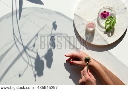 Hand Massage, Lymph Drainage With Green Jade Stone Roller. Moisturizing Cream On Marble Plate. Exoti