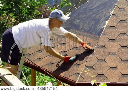 The Roofer On The Roof Of The Gazebo Compacts The Soft Tiles