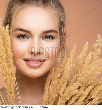 Closeup portrait of young smiling beautiful woman with a healthy  skin of a face. Happy Blonde girl with a bunch spring dry field flowers near the face - over colored background. Beauty face care.