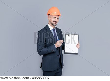 Architect Man In Businesslike Suit And Hardhat Showing Clipboard, Copy Space, Planning