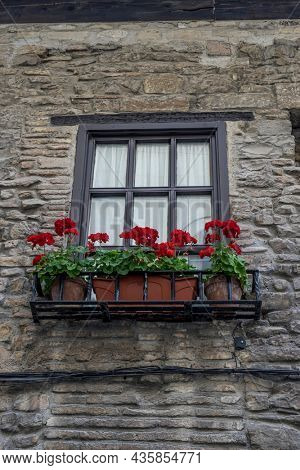 balcony with flowers, Facade of a medieval building in the center of Pamplona, ??medieval stone streets, typical and tourist alley of the city. Navarra Spain