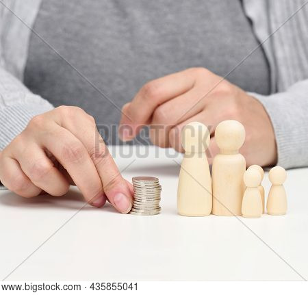 Hand Puts Coins In A Pile And Wooden Figurines Of A Family On A White Table. Economy And Investment