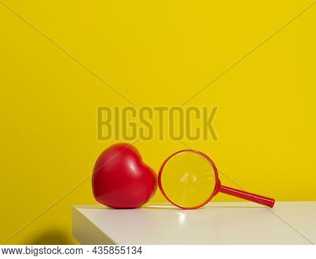 Red Plastic Heart And Magnifier On A White Table. Finding A Donor Organ
