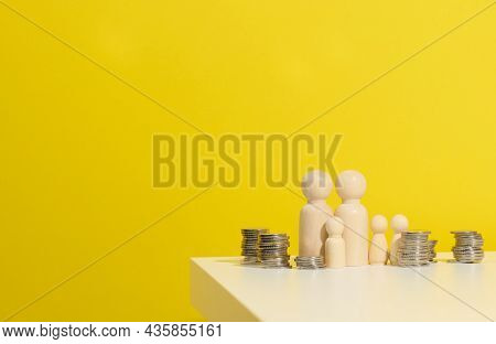 Stack Of Metal Coins And Wooden Figures Of Men On A White Table. Savings And Expenses, Family Budget