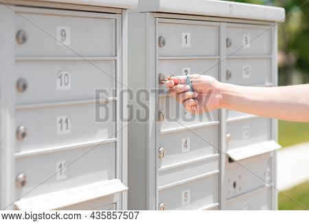 Person's Hand Holding Key Unlock-lock Mailbox By House Number, Selective Focus. Receiver Get Mail An