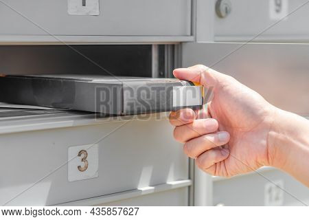 People Get Packet From Opened Cabinet Door. Mail Man Delivering Small Parcel In Mailbox By House Num