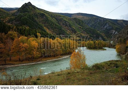 A Winding Bed Of A Beautiful Turquoise River Flowing Calmly At The Foot Of A High Mountain In Early
