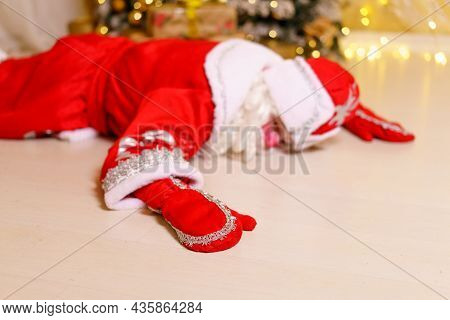 A Man Dressed As Santa Claus Lies On The Floor By A Christmas Tree With Gifts. Is Sleeping Or Restin