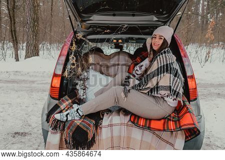 Brunette Woman Wrapped In Blanket In Trunk Car Drinking Coffee Tea From Thermos. Travel In Winter. C