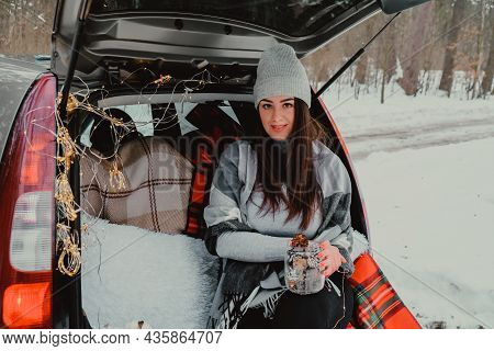 Brunette Woman Wrapped In Blanket In Trunk Car. Travel In Winter. Car Decorated With Festive Christm