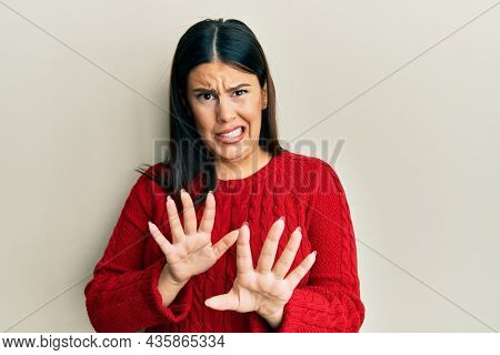 Beautiful brunette woman wearing wool winter sweater disgusted expression, displeased and fearful doing disgust face because aversion reaction. with hands raised