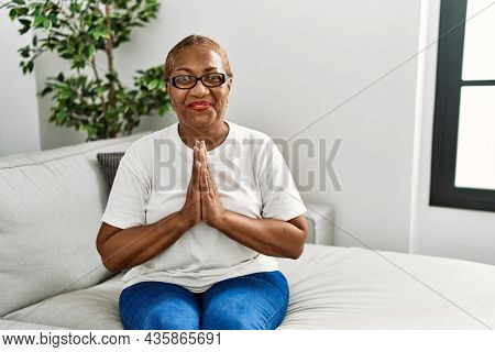 Mature hispanic woman sitting on the sofa at home praying with hands together asking for forgiveness smiling confident.