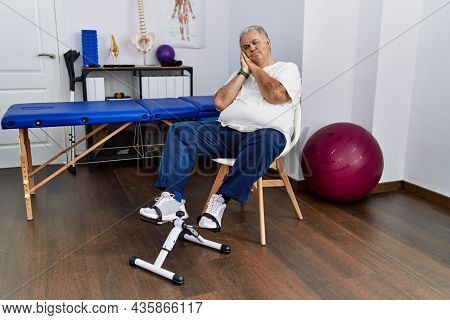 Senior caucasian man at physiotherapy clinic using pedal exerciser sleeping tired dreaming and posing with hands together while smiling with closed eyes.