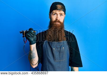 Redhead man with long beard tattoo artist wearing professional uniform and gloves relaxed with serious expression on face. simple and natural looking at the camera.