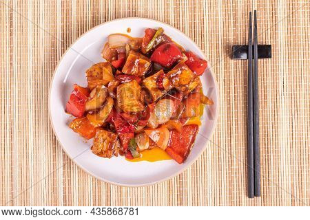 Stewed Tofu With Peppers And Onions In A Hot Pepper Sauce - Portion On A Plate With Chopsticks, Top