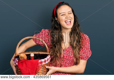 Young hispanic girl holding picnic wicker basket with bread winking looking at the camera with sexy expression, cheerful and happy face.