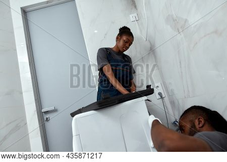 Low Angle Young Attractive Workwoman Watching Skilled Repairman Fixing Washing Machine. Female Appre