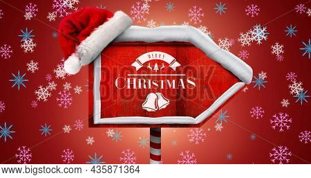 Image of falling snowflakes over wooden sign with merry christmas text. christmas, tradition and celebration concept digitally generated image.