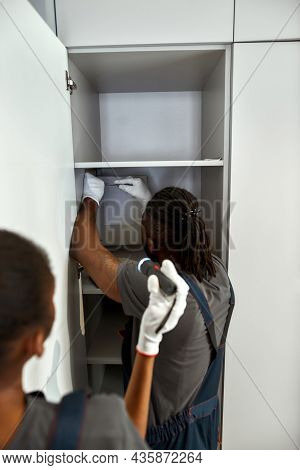 Back View Multiracial Man And Woman In Overalls Installing Domestic Fuse Box. Experienced Electricia