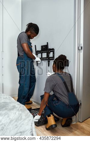 Handsome African Man In Workwear And Attractive Woman In Overalls Installing Mount Tv Using Screwdri
