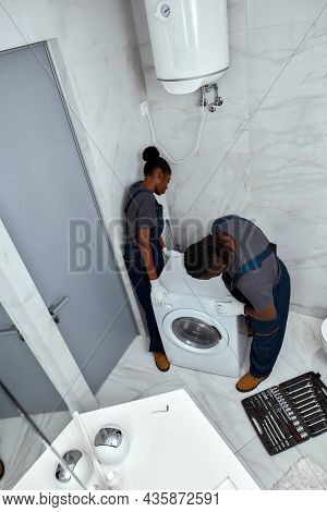 Above View Repair Man And Woman In Workwear Replacing Washing Machine Before Fixing It. Repair Servi