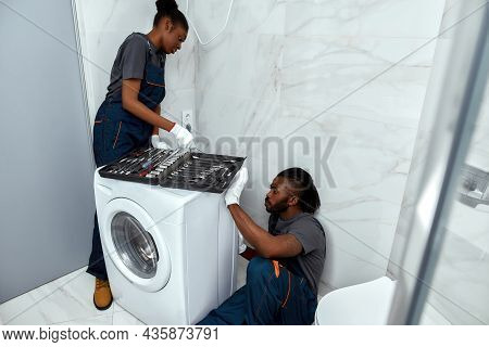 African Woman And Man In Overalls Repairing Washing Machine. Large Toolkit Placed On Machine, Young