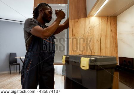 Side View Young Multiethnic Service Man In Overalls Checking Fridge With Flashlight. Repair Service